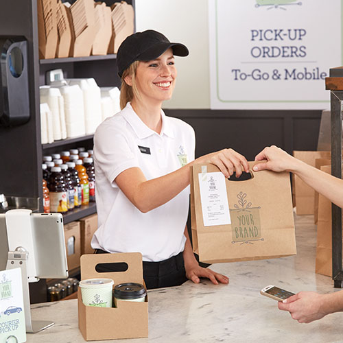 Restaurant employee handing an order to a delivery pro.