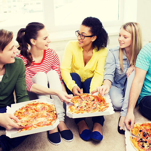 Friends enjoying delivery pizza.